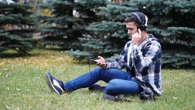 Young Male in headphones sitting on grass and tree, listening music stock video footage