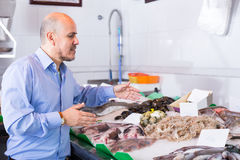 Smile man choosing cooled seafood in fish Royalty Free Stock Photos