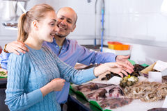 Smile man and girl choosing fish Stock Photos