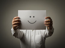Smile. Man hiding his face behind a white paper with a smiley face on it Royalty Free Stock Images