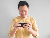 Smile man plays mobile game. stock image