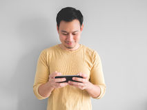 Smile man plays mobile game. stock images