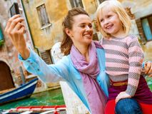 Happy mother and young daughter taking selfie in Venice royalty free stock photos