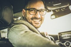 Smile is always with me. Young smiling business man driving car. Close up stock photo