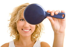 Smile in the mirror. Blonde woman looking into a hand mirror royalty free stock photography