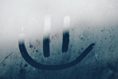 Smile on the misted window Stock Photo