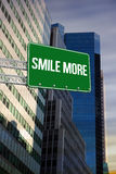 Smile more against low angle view of skyscrapers. The word smile more and green billboard sign against low angle view of skyscrapers Royalty Free Stock Photo