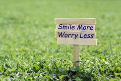 Smile more worry less. Wooden sign in grass,blur background Royalty Free Stock Image