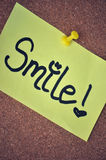 "Smile Note on Pinboard. Close up of a bright yellow post-it note pinned to a pinboard with a yellow thumb tac. The word ""Smile!"" is hand written on royalty free stock image"