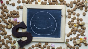 A smile painted for Dutch Santa-Claus. A smile painted on a chalkboard between ginger nuts and candy's for the Dutch Santa-Claus celebration of the 5th of Royalty Free Stock Photo