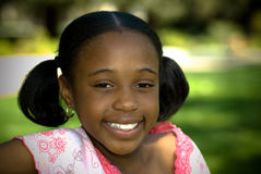 Smile In The Park. A young african american girl enjoys some shade in the park Royalty Free Stock Image