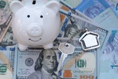 Smile piggy bank with home key chain on US dollar background. Saving for property investment concept. Insurance door real-estate agent capital loan achievement stock image