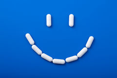 Smile of pills. Over blue royalty free stock photography