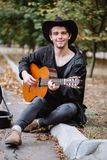 Smile and play music. On acoustig guitar in the park stock photography