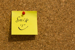 Smile on a post-it note. Smiling face on a yellow post-it note pinned to a noticeboard Stock Image