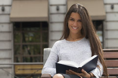 Smile and Read. Young pretty woman looking at the camera with a book in her hands.  The lady is seating in a wooden bench in front of a city building Stock Photo