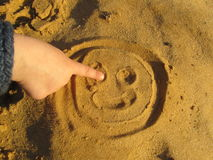 Smile in the sand. A child`s hand paints a smile on the sand stock photo