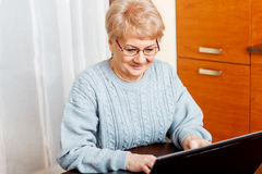 Smile senior sitting at table and using laptop Stock Photos