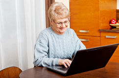 Smile senior sitting at table and using laptop Stock Photo