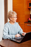 Smile senior sitting at table and using laptop Stock Image