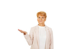 Smile senior woman holding something on open palm.  stock photo