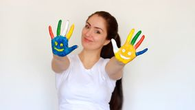 Smile. Smiles. Concept education, creativity, art and painting. Portrait student girl smiling girl showing painted. Multicolored hands with smiles on a light stock video footage