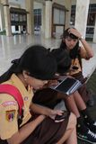 Smile student. Smiles student when enjoy communication with internet access from her smartphone and laptop Stock Photos
