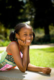 A Smile In The Sun. A young african american girl smiling in the park on a sunny day Royalty Free Stock Photo