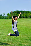 Smile teen open hands jumping. On the meadow Stock Photo