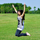Smile teen open hands jumping on the meadow. In summer Stock Images