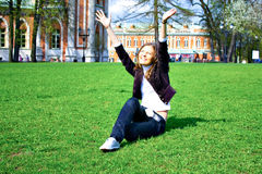 Smile teen open hands sitting on field. Smiling girl portrait outdoor in summer green park Stock Photography