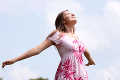 Smile teen open hands standing on field. Ful of flowers royalty free stock image