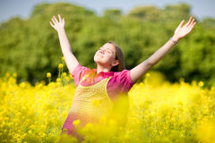 Smile teen open hands standing on yellow field. Soft focus. Focus on eyes stock photo