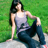 Smile teen sitting on the stone. In summer green park Royalty Free Stock Photo