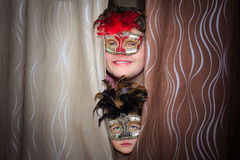 Smile teenage boy and unhappy little girl in theatrical masks. Happy smile teenage boy and unhappy little girl in theatrical masks watching from behind of Royalty Free Stock Image