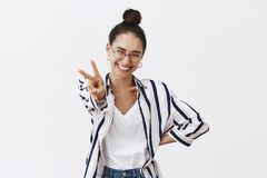 Smile to future. Portrait of optimistic beautiful and joyful woman in glasses and stylish shirt, pulling hand with peace. Sign towards camera, smiling broadly royalty free stock photos