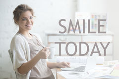 Smile today. Motivational image. Portrait of beautiful happy smiling young designer woman sitting at home office desk with cup of coffee. Attractive cheerful Royalty Free Stock Image