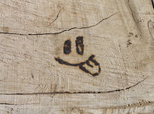Smile with tongue burned into wood Royalty Free Stock Photo