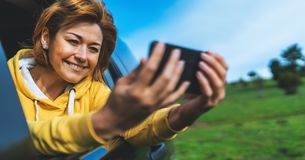 Smile tourist girl in an open window of a auto car taking photo selfie on mobile smart phone, person looking on camera gadget. Technology, blogger using content royalty free stock photography
