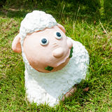 Smile white sheep statue in green grass Stock Photography
