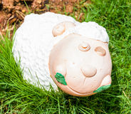 Smile white sheep statue in green grass Stock Photo