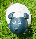 Smile white sheep statue in green grass Stock Images
