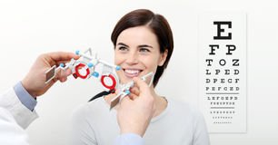 Smile woman doing eyesight measurement with trial frame and visu Royalty Free Stock Photos