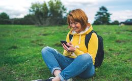 Smile woman holding in female hands gadget technology, tourist young girl on background green grass using mobile smartphone, hiker. Texting finger message on stock images