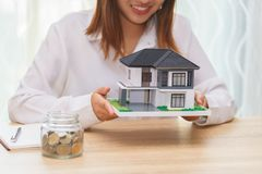 Smile woman holding home model and getting ready to buy house - stock image
