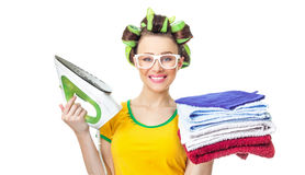 Smile woman holding iron and towels. Stock Photo