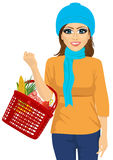 Smile woman holding a shopping basket full of food Royalty Free Stock Image