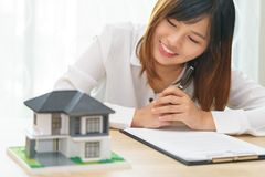 Smile woman looking at home and getting ready to sign contract f royalty free stock images