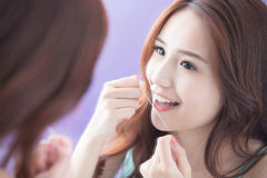 Smile woman with teeth floss. Close up of Smile woman clear teeth by floss and look mirror. great for health dental care concept. asian beauty Royalty Free Stock Photo