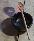 Smile. Wooden spoon skimmer, highlighted in red with slits in the form of smiles and its ominous shadow on the old wooden dirty white floor. Black wooden bowl Royalty Free Stock Photo